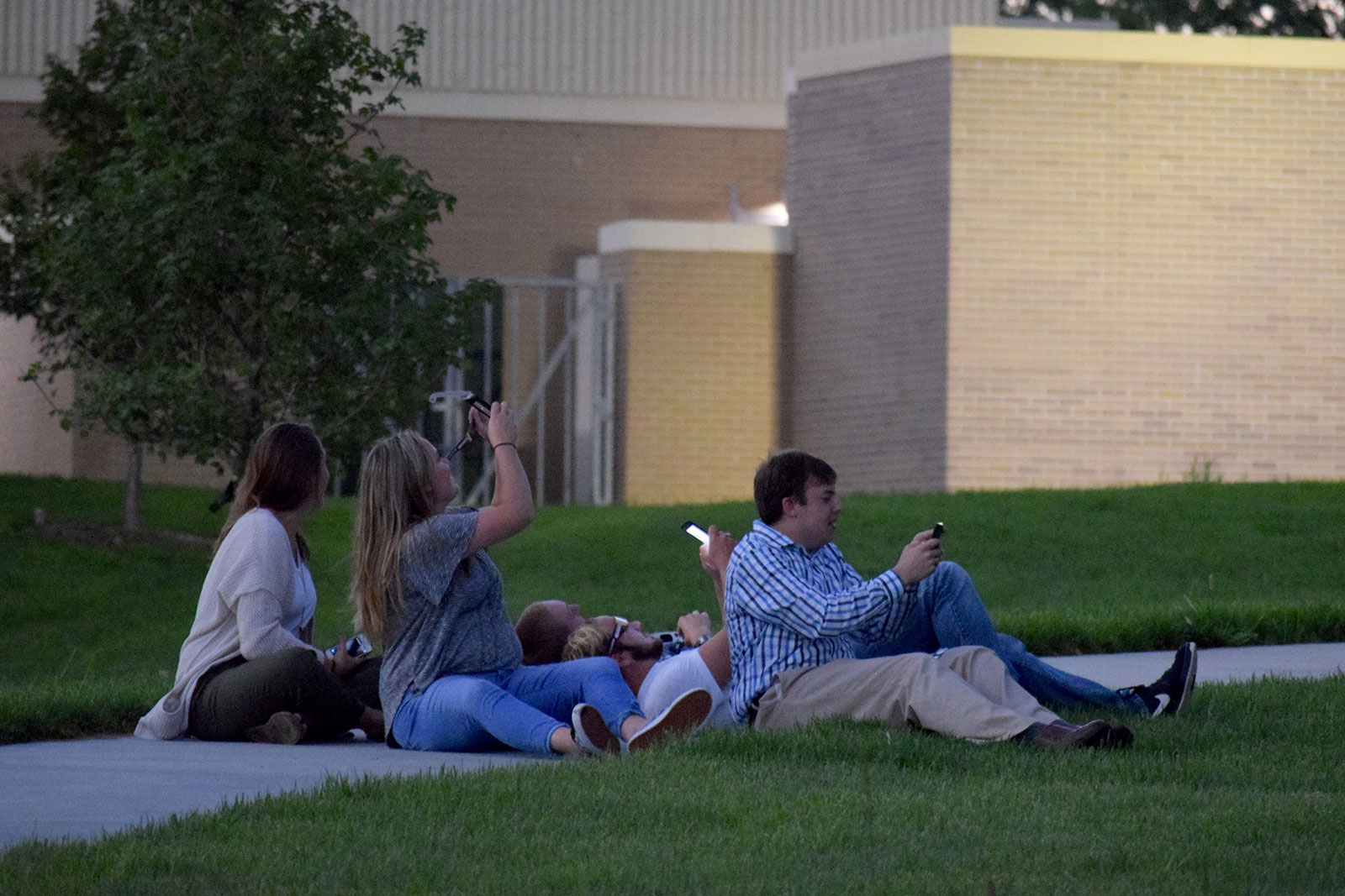 A group of veterinary students watch the eclipse on the sidewalk outside the Nebraska Veterinary Diagnostic Center.