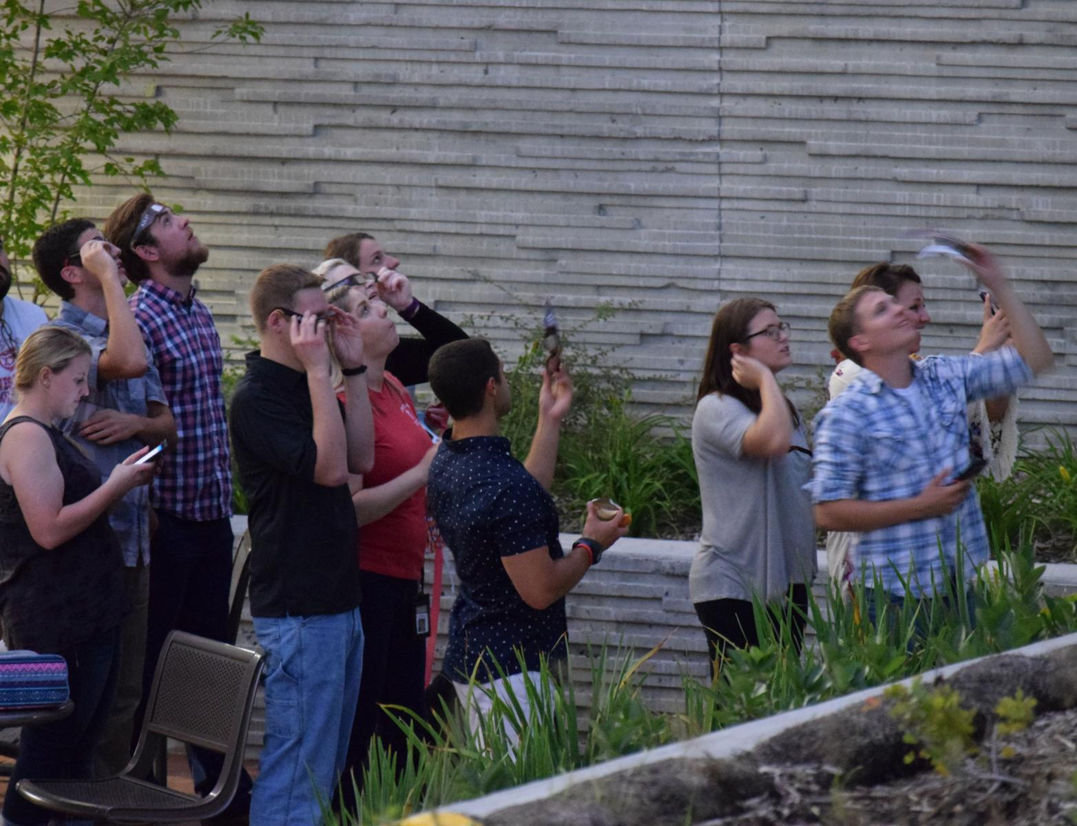 Veterinary students watch the eclipse from the courtyard of the Nebraska Veterinary Diagnostic Center.