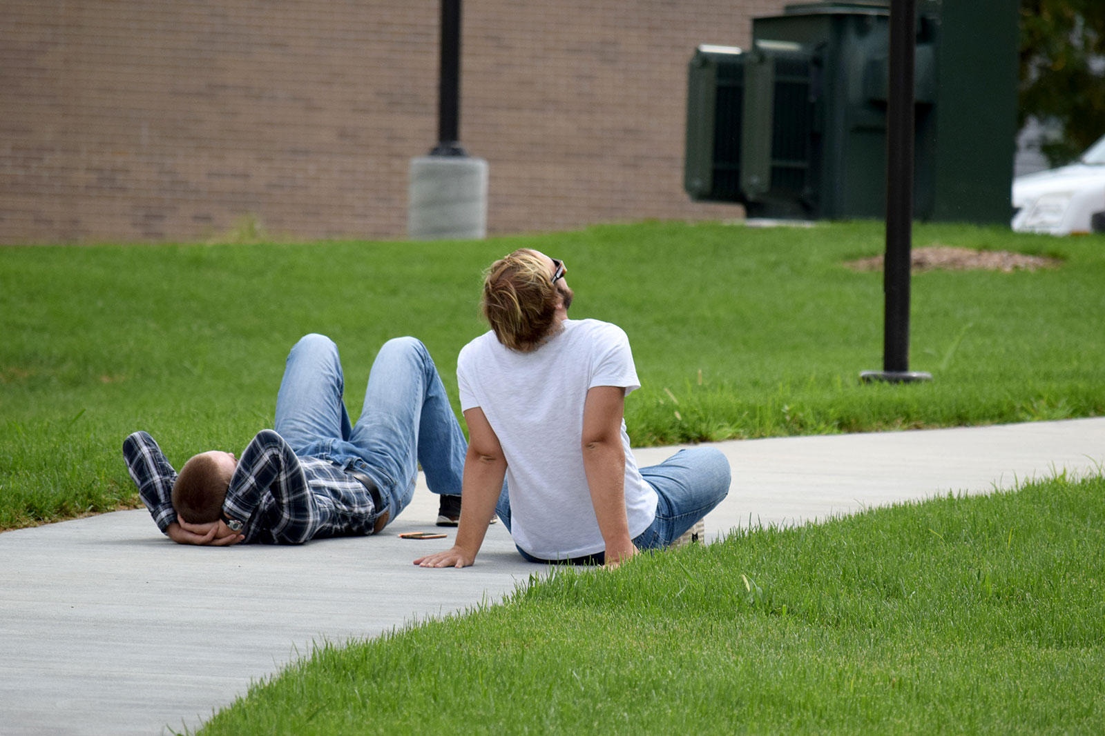 Two veterinary students sit on the sidewalk to watch the eclipse.