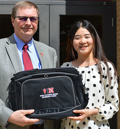 Dr. Don Reynolds presents Ting Jia with a graduation gift