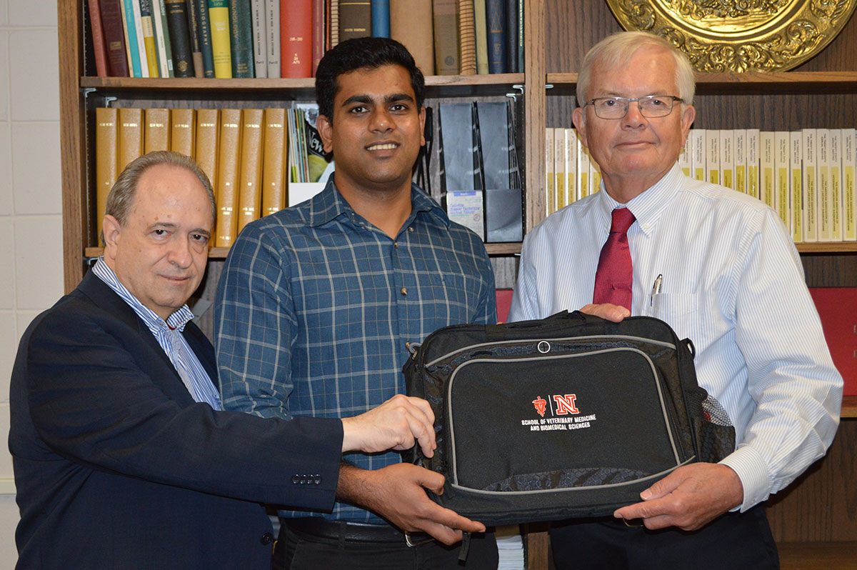 Gov Rathnaiah is presented with a computer bag, by his adviser Raul Barletta and director of the School Clayton Kelling.