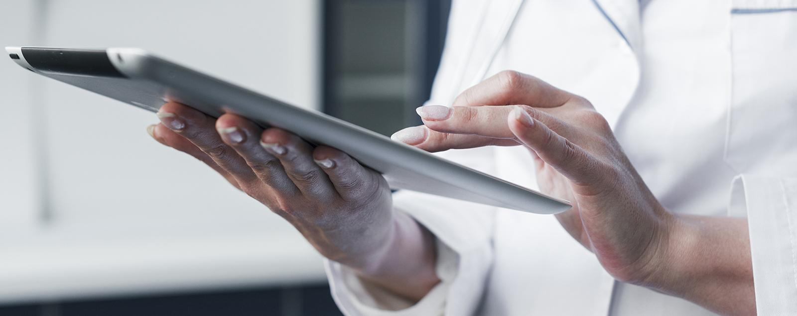 Person in lab coat working on an iPad.